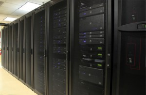 Several racks of 1u and 2u servers in black cabinets in a computer operations room.